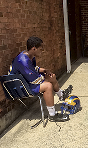 Nansemond-Suffolk Academy's Jordan Houston take a break to sit in the shade after their two early practices. The Saints' new football coach Michael Biehl moved practices to begin early in the morning to beat the heat.