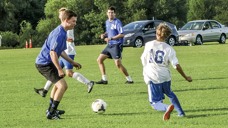 Angelo Tortellini, an eighth grader, faces off against an alumni team featuring his coach, Patrick Whelan. Though the game ended 2-2, Whelan declared the alumni team victors.