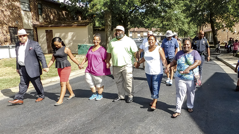 City officials, police officers and Cypress Manor Apartments residents joined hands for a community walk after the Suffolk Redevelopment and Housing Authority's community panel.