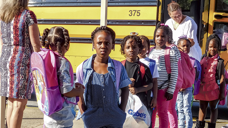 A group of Driver Elementary School students files off the bus.