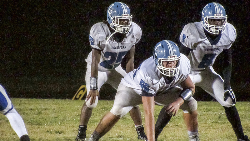 Lakeland High School seniors Riley Richardson(55) Demontria Milteer (25) and Demitrius McKinney (8) line up for a play against Wilson High School in Portsmouth on Friday. The Cavaliers won the game 28-8.