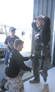 Joshua Ferguson, who lost his left leg to an improvised explosive device in Iraq, gets suited up for his skydive at Skydive Suffolk with the help of Ron Conderey.